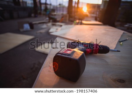 Screw gun is lying on plywood, beautiful light - the end of the hard day workshop - stock photo