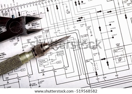 Screwdriver and nippers on a schematic diagram background