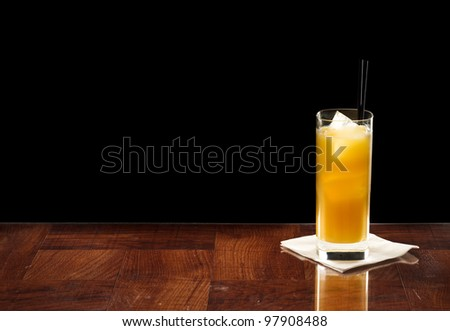 screwdriver cocktail on a bar top isolated on a black background - stock photo