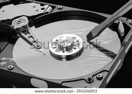 Screwdriver destroying a hard disk drive platter to erase the data - stock photo