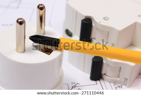 Screwdriver, work tools, electric plug and fuse lying on construction drawing of house, accessories for engineering work - stock photo