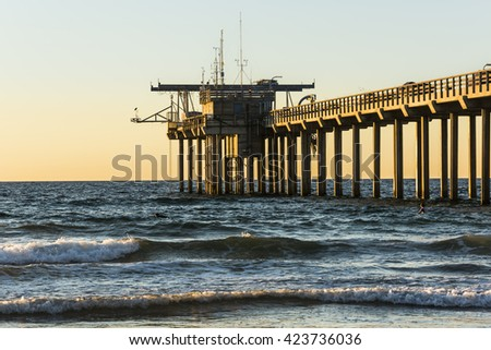 Scripps Pier during sunset with swimming surfers in La Jolla, San Diego, California - stock photo
