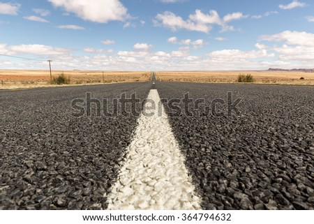 Scrubland with dry grass, red sand stretches for miles on either side of the long straight road to rocky mountain plateaus, blue sky and huge cumulus clouds, Northern Cape, South Africa - stock photo