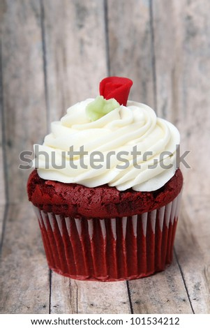 Scrumptious Red Velvet cupcake on a wooden floor background. - stock photo