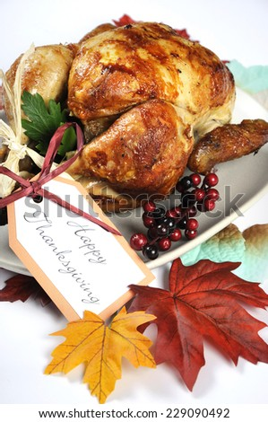 Scrumptious roast turkey chicken on platter with festive decorations for Thanksgiving lunch with autumn Fall leaves on white table. Closeup. - stock photo