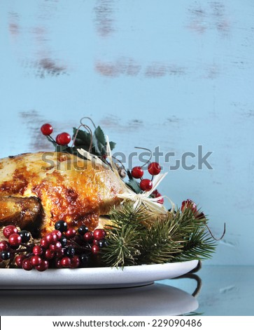 Scrumptious roast turkey chicken on platter with festive decorations for Thanksgiving or Christmas lunch, against shabby chic aqua blue rustic wood background. Vertical with copy space. - stock photo