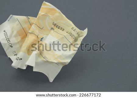 scrunched blank cheque on a grey background - stock photo
