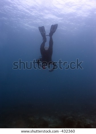 Scuba diver diving head first into the ocean - stock photo