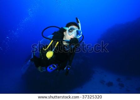 Scuba Diver explores a coral reef - stock photo