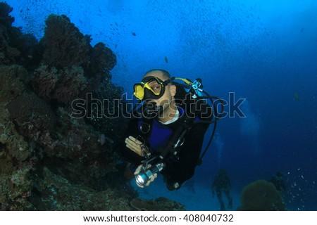 Scuba diver explores coral reef underwater - stock photo