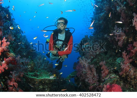 Scuba diver exploring coral reef underwater - stock photo