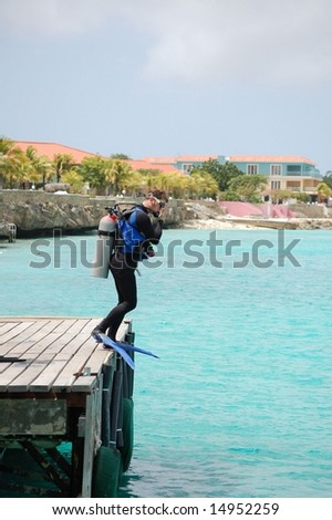Scuba diver ready to leap off dock. - stock photo