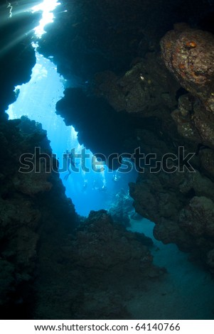 Scuba diver silhouette outside an underwater cave. Jackfish alley, Ras Mohamed National Park, Red Sea, Egypt.