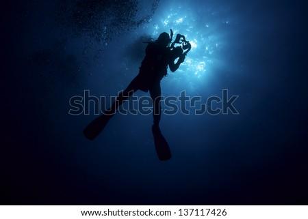 Scuba Diver Silhouette with Video Cam - stock photo