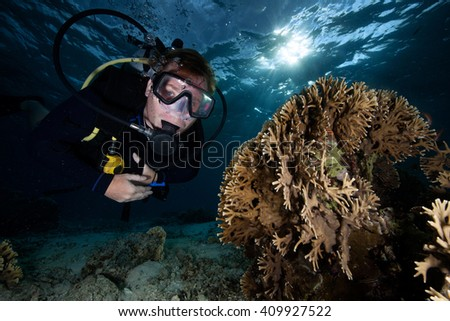 Scuba Diver Swimming at the Coral Reef - stock photo