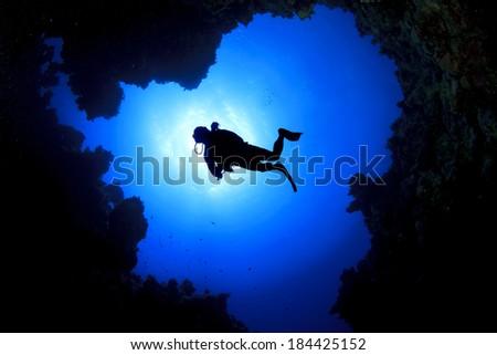 Scuba Diver swims over underwater cave, silhouette against sun - stock photo
