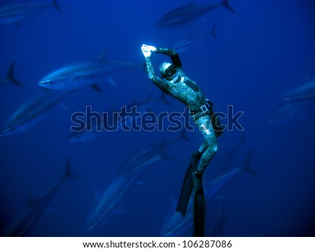 Scuba diver swims with fishes - stock photo