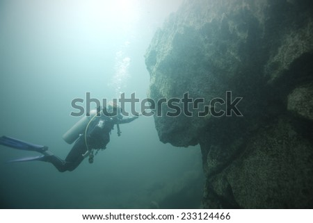 Scuba diver toward a rock in Lake Barracuda, Coron Island, Palawan. The rock looks like sphinx statue in a specific angle. - stock photo