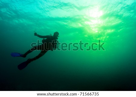 SCUBA diver under the surface at sunset, with the glow of the dying sun. Taken in the Wakatobi, Indonesia.
