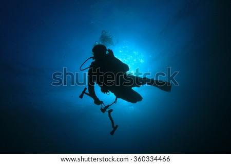 Scuba diver underwater photographer black on blue silhouette against sun - stock photo