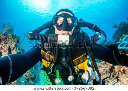 SCUBA diver with a closed circuit rebreather on a tropical coral reef - stock photo