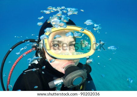 Scuba diver with bubbles looking at copy space for your text. - stock photo