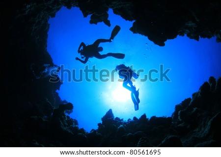 Scuba Divers descend into an Underwater Cavern. Silhouettes against sunburst - stock photo