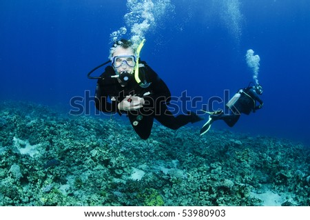 scuba divers enjoying a dive - stock photo