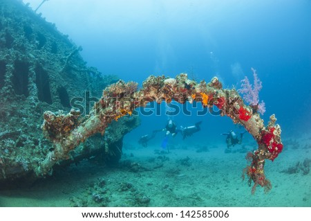 Scuba divers exploring an old underwater shipwreck in a tropical ocean - stock photo