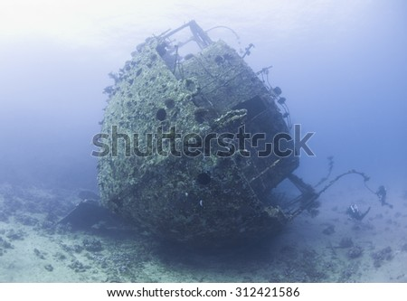 Scuba divers exploring the stern section of a large underwater shipwreck - stock photo