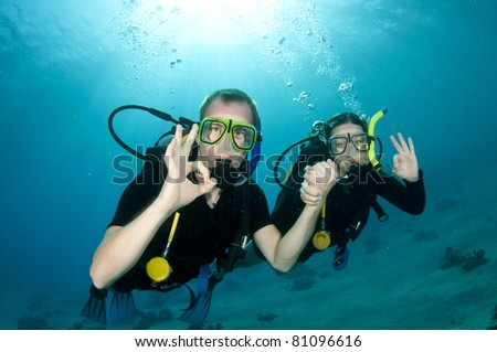 Scuba divers give OK sign - stock photo