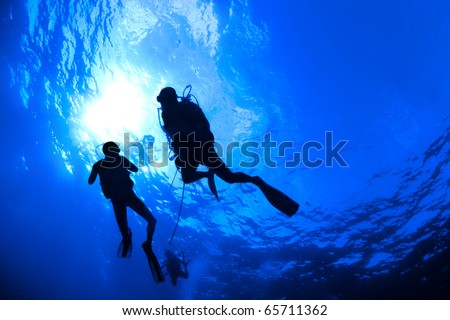 Scuba divers in silhouette swimming under water in the ocean near the surface backlit by a sun burst. Horizontal photo. - stock photo