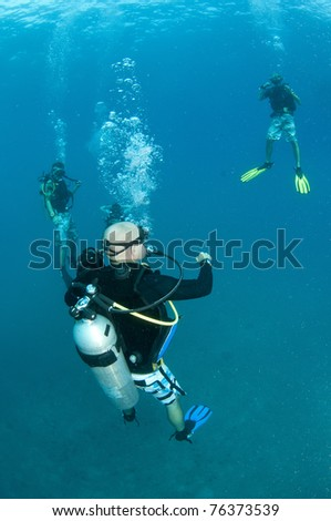 scuba divers on coral reef in Thailand