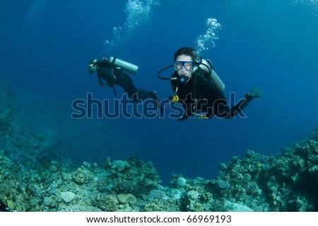 scuba divers scuba dive in ocean and have fun - stock photo