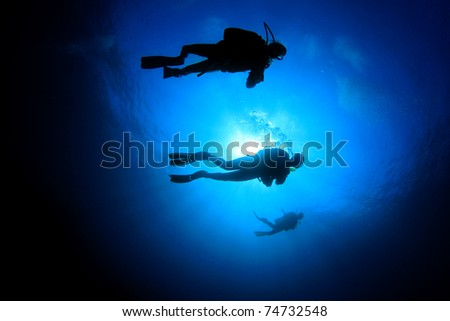 Scuba Divers silhouettes against sun in blue water - stock photo