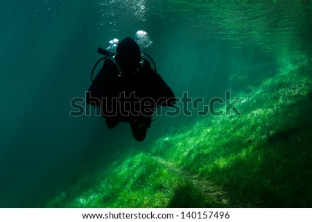 Scuba Diving Alps lake. Cold crystal clear, emerald water with sun-rays. Austria. Sunken Park. - stock photo