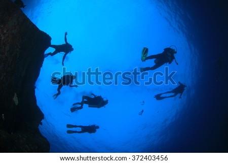 Scuba diving exploring coral reef underwater sea ocean - stock photo