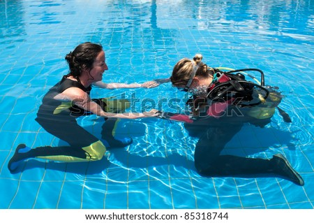 Scuba diving instructor and student in a swimming pool - stock photo
