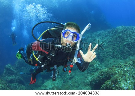 Scuba diving instructor leads a group of divers - stock photo