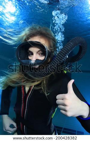 Scuba woman with black neoprene dive suit underwater  - stock photo