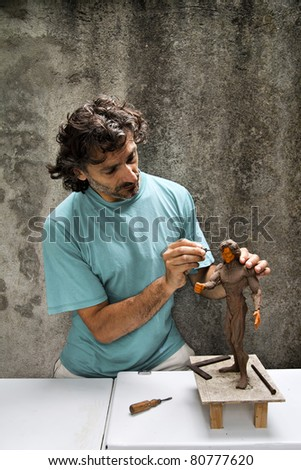Sculptor at work on a human figurine