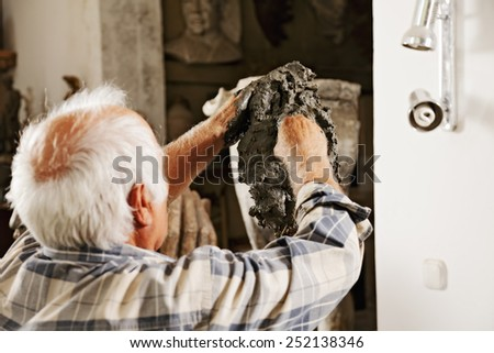 Sculptor making sculpture rear view - stock photo