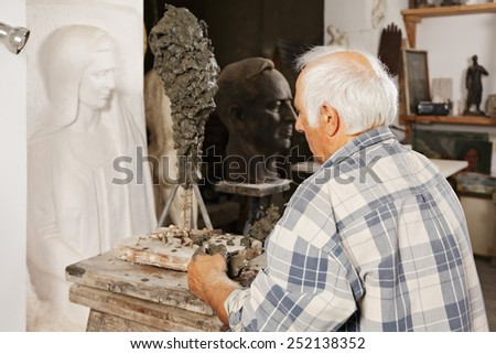 Sculptor standing at his new work in a workshop - stock photo