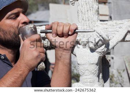 Sculptor working on a Jesus stone sculpture. - stock photo
