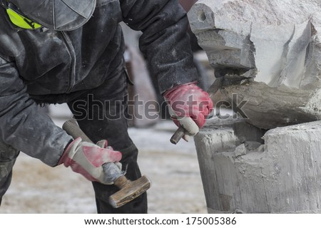 sculptor working on a large stone sculpture - stock photo