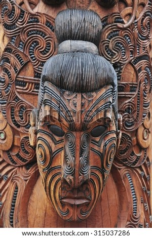sculpture and design on pole of Maori face-figure sculpture. Selected focusing with shallow DOF. - stock photo