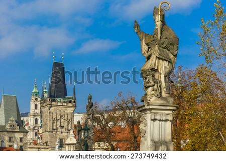 Sculpture of St. Augustine with a burning heart in hand trampling heretical books on Charles Bridge in Prague, Czech Republic. Shallow depth of field, focus on foreground - stock photo