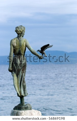 Sculpture of the woman and seagull with the sea in the background - stock photo