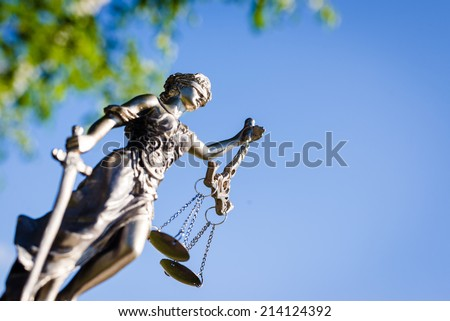 sculpture of themis, femida or justice goddess on bright blue sky outdoor copyspace background - stock photo