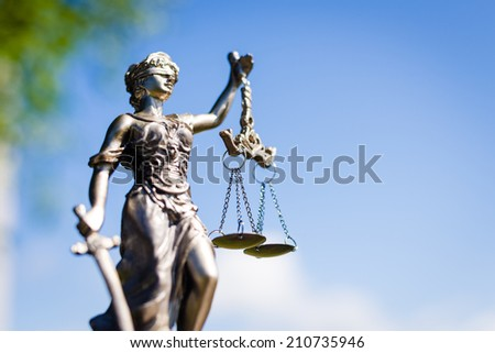 sculpture of themis, femida or justice lady goddess on bright blue sky outdoors copyspace background - stock photo